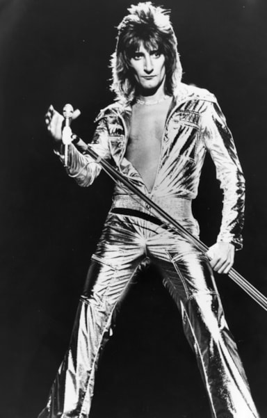 London born rock star, singer Rod Stewart, in a spectacular silver jumpsuit during the recording of his own television spectacular 'A Night On The Town'.   (Photo by Central Press/Getty Images)