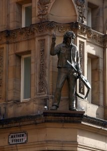 LIVERPOOL, UNITED KINGDOM - FEBRUARY 01: A statue of John Lennon adorns the facade of the newly opened Hard Days Night Hotel on February 1, 2008, Liverpool, England. The new Hard Days Night Hotel is a four star boutique hotel set in the heart of Liverpool's 'Beatles Quarter' near the world famous Cavern Club where the Beatles first rose to fame. The hotel features 110 rooms, including luxury and deluxe rooms and has two stunning penthouses - the specially designed Lennon & McCartney suites - the Lennon featuring a white grand piano. Specially commissioned artwork, created by acclaimed Beatles artist Shannon, adorns the 110 guest bedrooms and public rooms. (Photo by Christopher Furlong/Getty Images)
